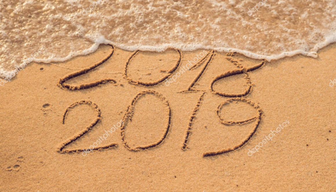 New Year 2019 is coming concept - inscription 2018 and 2019 on a beach sand, the wave is almost covering the digits 2018
